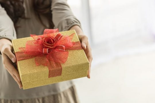 happy-new-year-holiday-seasonal-concept-close-up-beautiful-gift-box-holding-present